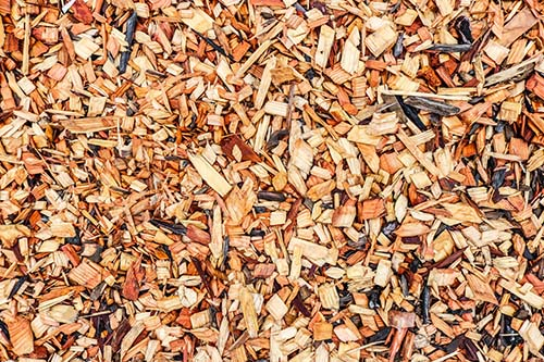 "Wood chip mulch displayed in Spoken Garden's ""How to Mulch in 6 Basic Steps"" post"