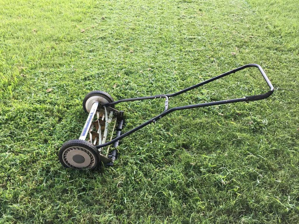 "A human-powered lawn mower is shown on a green lawn in Spoken Garden's ""Top Fall Garden Tasks"" post."
