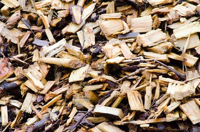 "A pile of wood mulch in a garden bed in Spoken Garden's ""Fall Garden Tasks"" post."