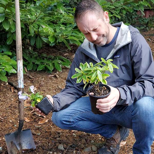 Man looking at plants in pots he is holding in his hands while squatting down towards the ground.
