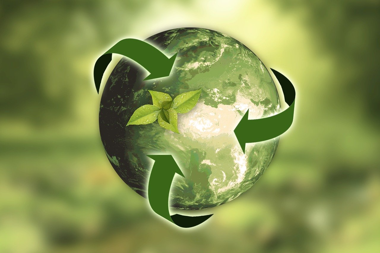 Planet earth being circled by green arrows all curving around the planet to show the interconnectedness of what we do here impacts our environment.