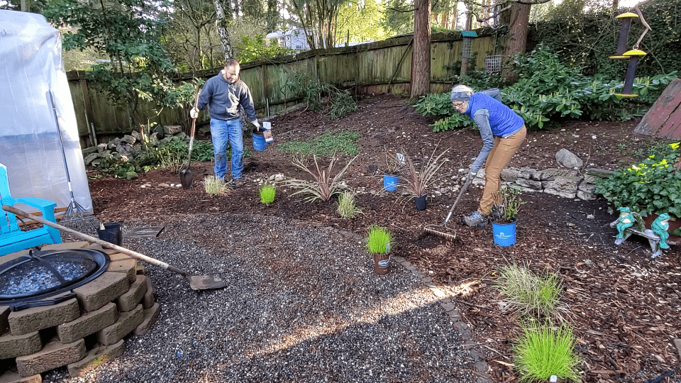 two gardeners planting plants in the ground around other plants in a pattern and design.