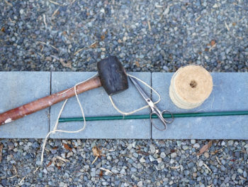 Staking supplies of a rubber mallet, twine, metal green stake, and scissors all grouped together on a concrete pavers.